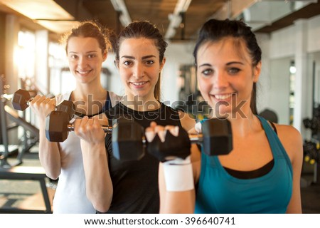 Three fit and beautiful young women lifting weights in a fitness club. Focus on girl in the center. - stock photo