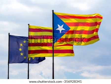 Three flags fluttering together on a windy day: the flag of the European Union, the ancient flag of Catalonia and the starry catalan flag. - stock photo