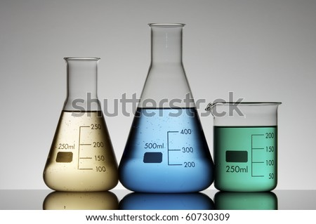 three flasks to measure liquids in a chemical laboratory - stock photo