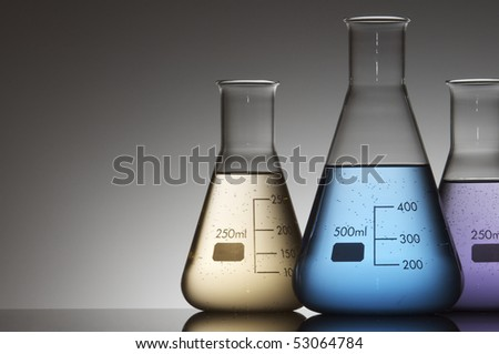 three flasks with colored liquid and a white background