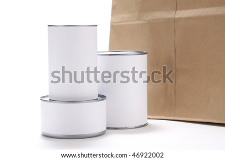 Three food cans with blank white labels in front of a brown paper grocery bag. - stock photo