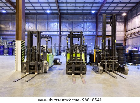 Three forklift in the large modern warehouse - stock photo