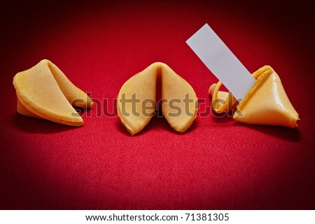 Three fortune cookies, one broken with blank message on red background. - stock photo