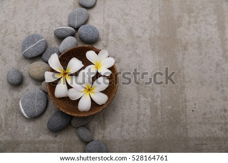Three frangipani in wooden bowl with spa stones on grey background.