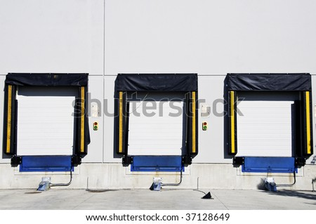 Three freight  loading doors with a set of green and red light to aid driver. - stock photo
