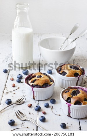 three french clafoutis with blueberries and cherries on ceramic ramekins on rustic white vintage background with milk glass bottle and bowl - stock photo