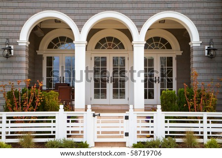 Three french door entrance to grey house with white trim and deco style fence