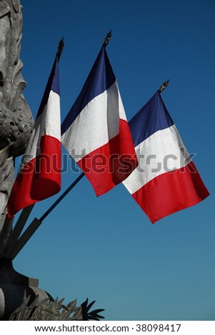 Three French tricolors adorn a war memorial in SW France - stock photo