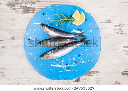 Three fresh anchovy fish on blue round kitchen board on white wooden table, top view. Culinary seafood concept. Delicious healthy eating. - stock photo
