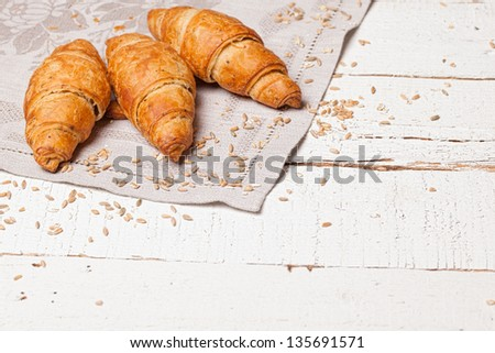 Three fresh baked bread on white wooden table
