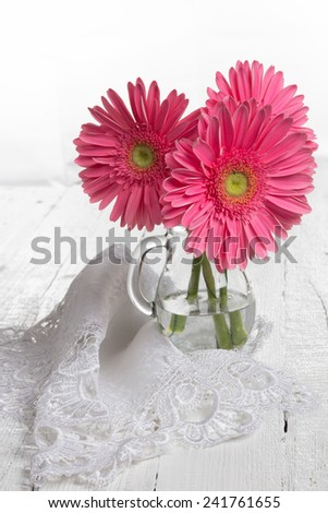 Three fresh, beautiful gerbera flower the old white table - stock photo