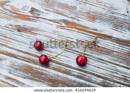 Three fresh cherry on old wooden table. Healthy and tasty food on white background. - stock photo