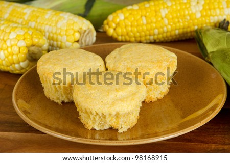 three fresh corn muffins with ingredients on a homestyle plate - stock photo