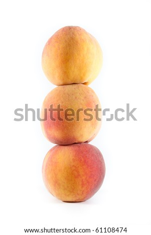 Three fresh fuzzy yellow and orange peaches stacked on each other on a white isolated background. - stock photo