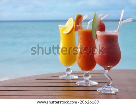 three fresh juices cocktails orange , watermelon and papaya on the table on the beach. Summer, vacation, healthy life, ocean - stock photo