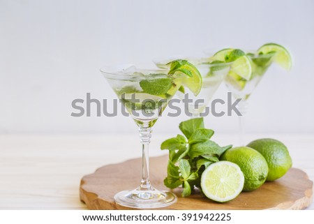 Three fresh mojitos cocktail. Mojitos with mint leaves, lime and ice - stock photo