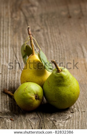 Three fresh pears on old wooden table