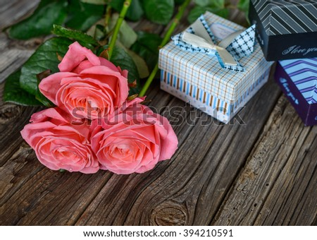 Three fresh pink roses with a Valentines, wedding, anniversary, Mothers Day or birthday gift on a rustic wooden table with copy space - stock photo