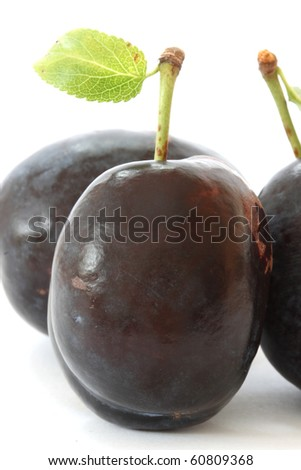 Three fresh plums on white background