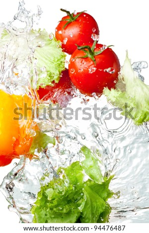 Three Fresh red Tomatoes, Yellow Bell Pepper and lettuce in splash water Isolated on white background - stock photo