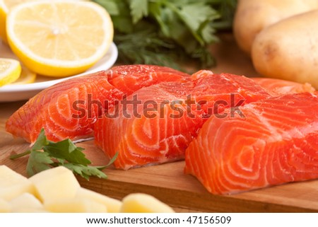 Three fresh salmon pieces with lemons on a cutting board - stock photo