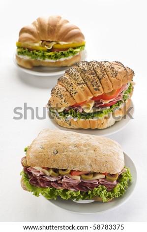 Three fresh sandwiches on plates close up shoot - stock photo