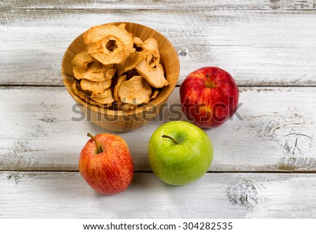 Three fresh whole apples and a bowl of dried apple chips on rustic white wood.  - stock photo