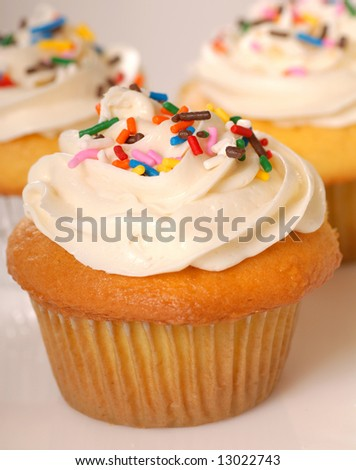 Three freshly baked vanilla cupcakes with lemon buttercream and sprinkles
