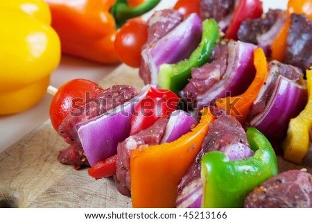 Three freshly prepared beef shish-ka-bob with vegetables, marinated and ready for the grill.   Shallow depth of field. - stock photo