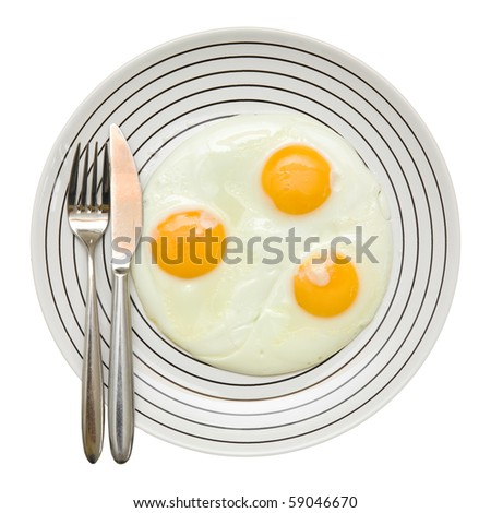three fried unbroken eggs on white plate with black stripe; fork and knife on the left,  shot from the top; isolated; - stock photo