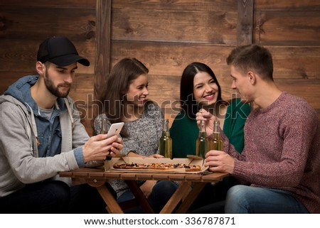 Three friend discussing their businesses while the man in cap looking at his stupid mobile phone. People resting in the restaurant. - stock photo