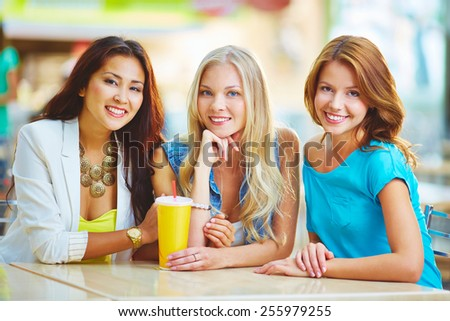 Three friendly girls having drink in cafe - stock photo