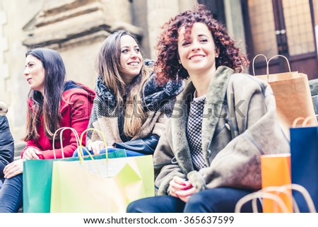 Three friends after shopping in around the city are resting on the steps of a stairway with all the bags of purchases - stock photo