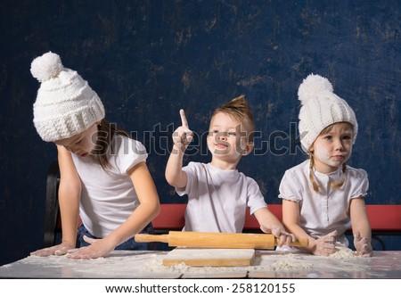 Three friends are preparing dough - stock photo