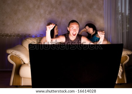 Three friends are watching TV - stock photo
