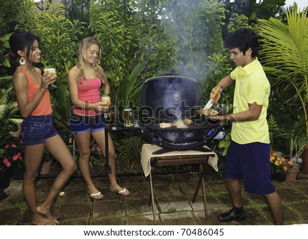 three friends at a barbecue party in hawaii cooking chicken on the grill