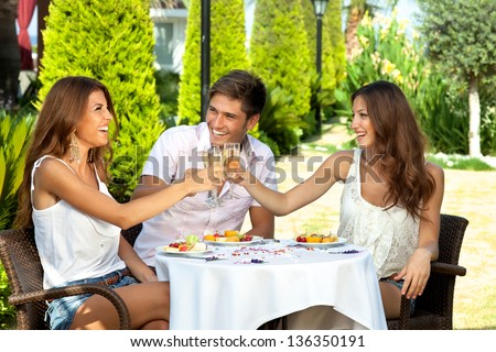 Three friends celebrating seated at an outdoor table in the garden toasting each other with champagne and enjoying a healthy tropical fruit meal - stock photo