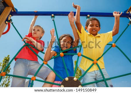 Three friends climbing the net - stock photo