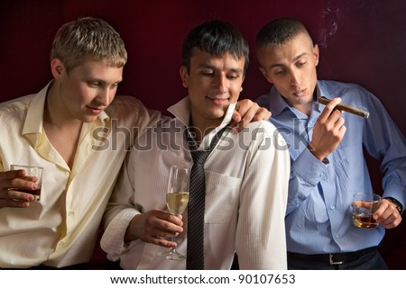 Three friends drinking a whisky and smoking a cigar - stock photo
