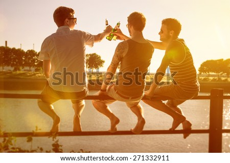 Three friends drinking beer - stock photo