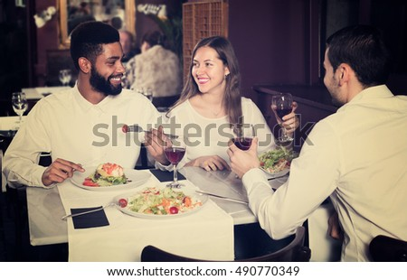 Three friends eating at restaurant table and chatting