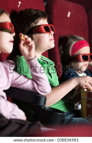 Three friends eating popcorn in the movie theater - stock photo