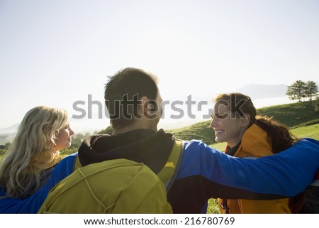 Three friends enjoying the evening view. - stock photo