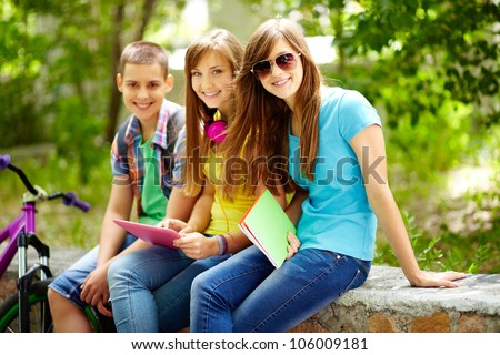 Three friends enjoying their free time after school classes - stock photo
