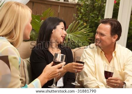 Three Friends Enjoying Wine on an Outdoor Patio. - stock photo