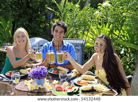 three friends having a barbecue lunch in their tropical garden and raising their glasses in a toast.