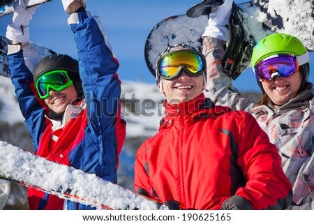 Three friends holding snowboards and skies