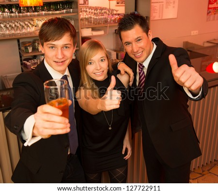 Three friends in a bar showing thumbs up - stock photo