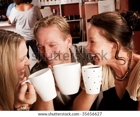 Three friends in a coffee house toasting with their cups - stock photo