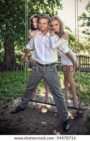 Three friends in a garden on the swing - stock photo